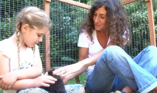 Mother And Daughter Petting A Pet