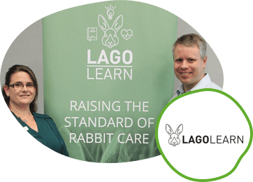 Two people standing in front of a Lago Learn banner